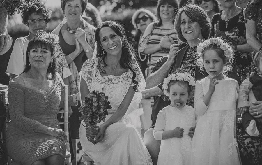 The bride sits on a chair next to her family during the outdoor wedding ceremony at Micklefield Hall
