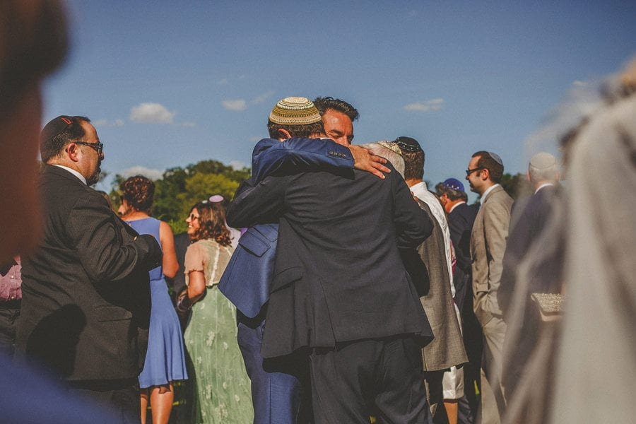 Wedding guests embrace the groom in the gardens at the outdoor wedding ceremony at Micklefield Hall