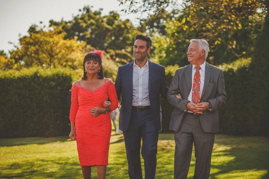 The groom and his parents walk across the garden during the outdoor wedding ceremony at Micklefield Hall