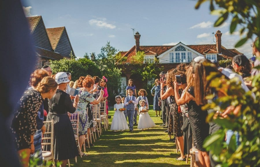 The flower girls and paige boy walk up the aisle for the outdoor wedding ceremony at Micklefield Hall