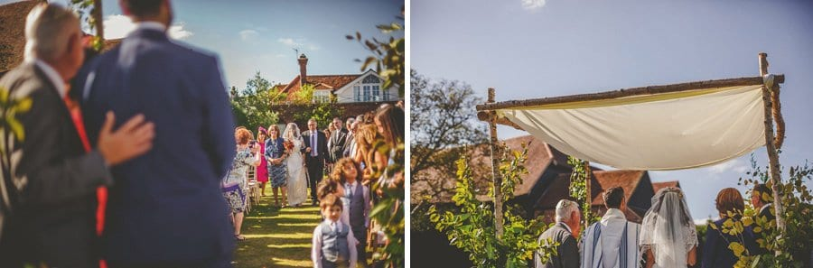 The groom watches as the bride and her parents walk up the aisle for the outdoor wedding ceremony at Micklefield Hall