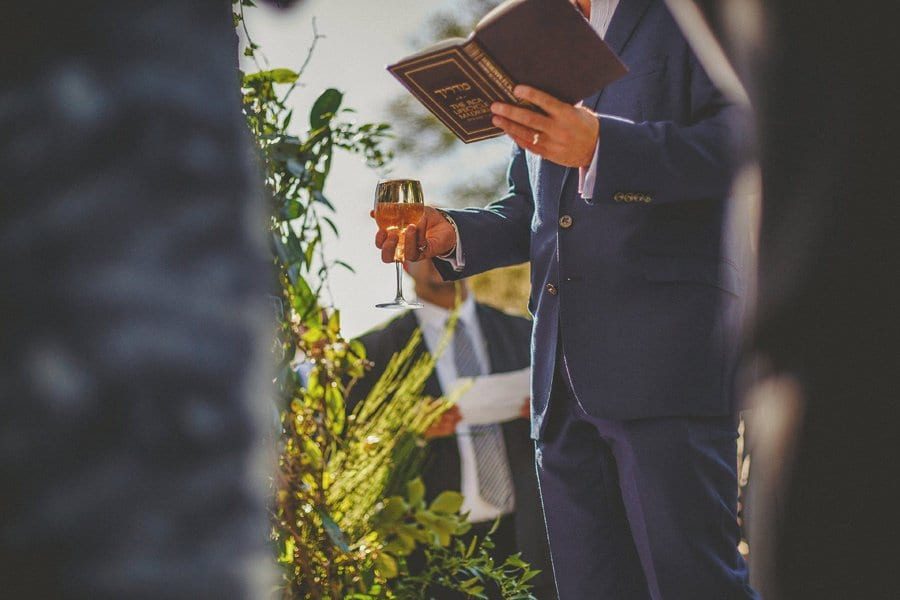 A man stands and holds a book in his left hand and a glass of wine in his right hand during the outdoor wedding ceremony at Micklefield Hall