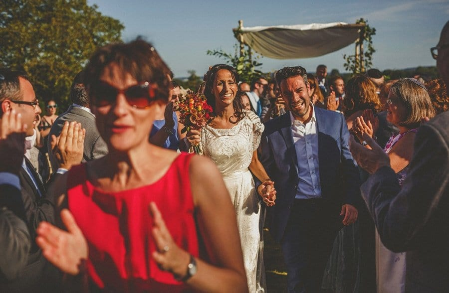 The bride and groom walk down the aisle together at the end of the outdoor wedding ceremony at Micklefield Hall