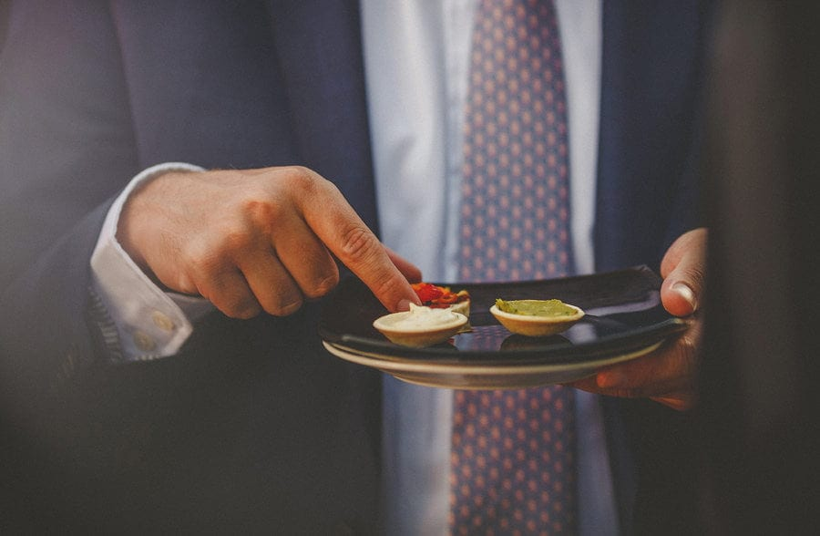 A wedding guest holds a plate with canapes on them
