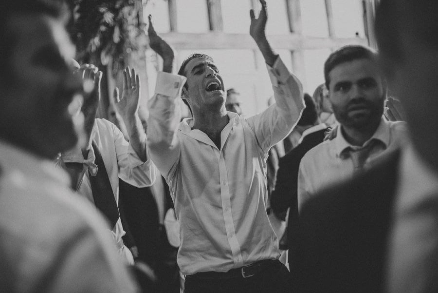 A wedding guest claps his hands in the barn on the dancefloor