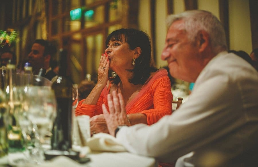 The groom's mother kisses her hand as she sits at the wedding table and listens to her sons wedding speech