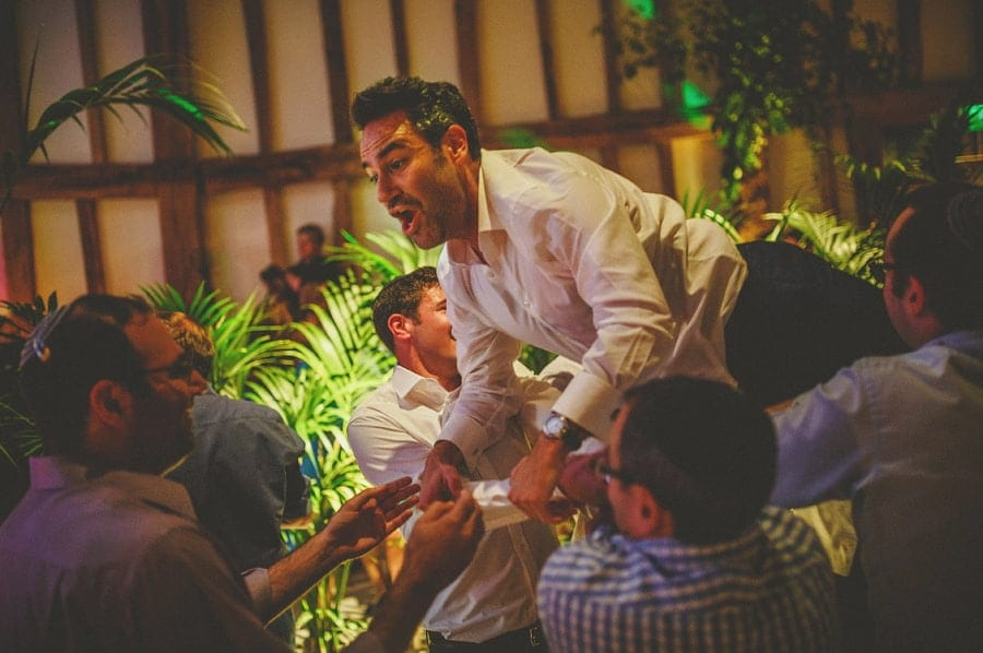 The groom's friends lift the groom over their shoulders on the dancefloor