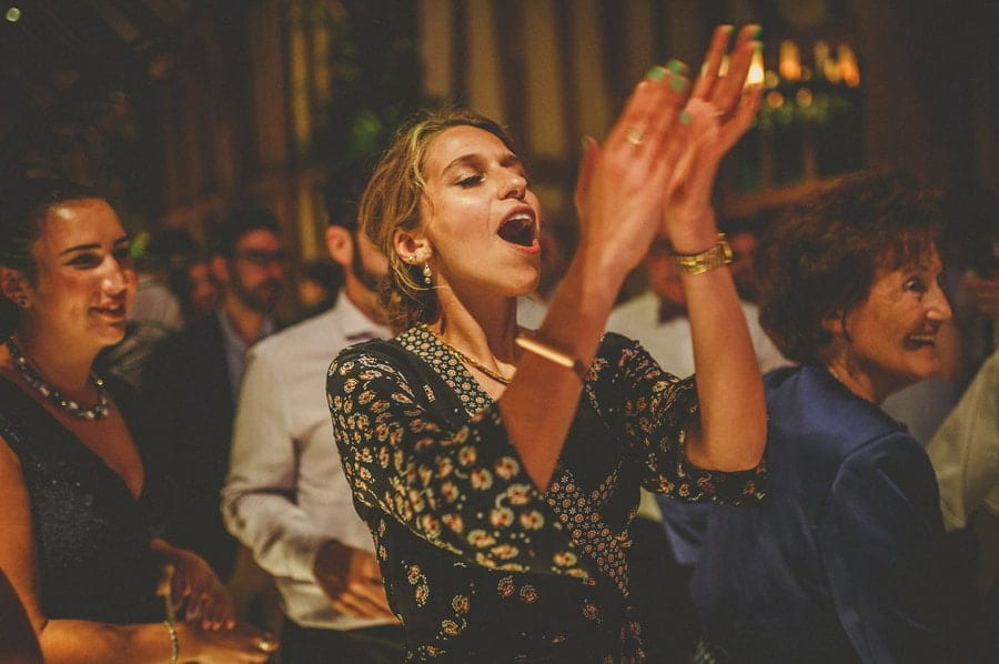 The bride's sister claps her hands on the dancefloor in the barn at Micklefield Hall