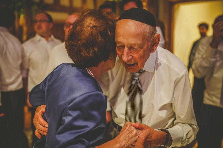 The bride's grandparents hold each others hands and dance together