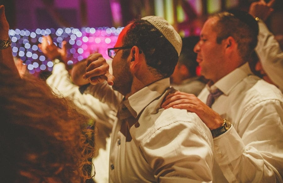 Wedding guests stand close to each other on the dancefloor at Micklefield Hall