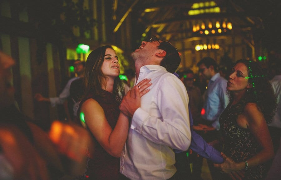 A husband and wife dance together on the dancefloor in the barn