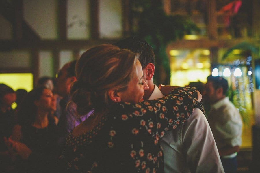 The bride's sister embraces her husband in the barn at Micklefield Hall