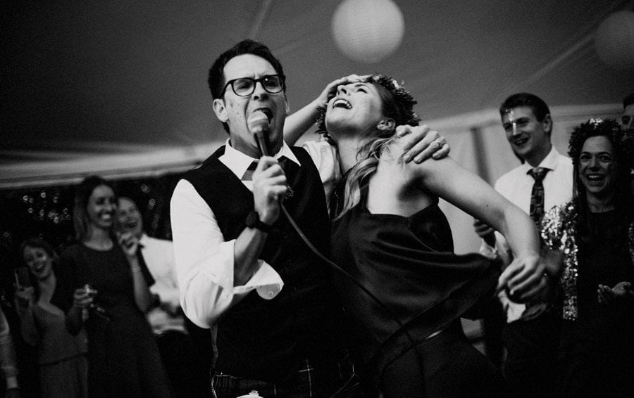 A man sings into a microphone and wraps an arm around a lady on the dancefloor of the marquee