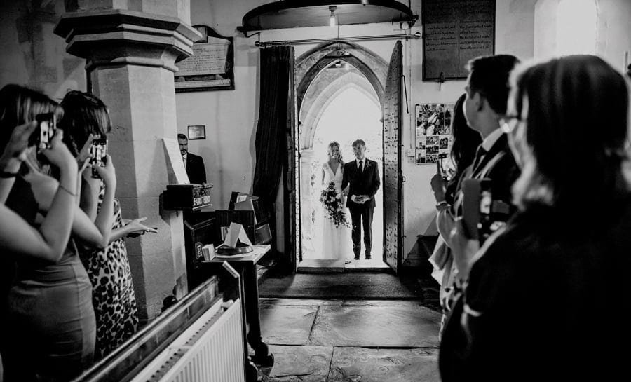 The bride and her father stand at the door of the Church as wedding guests stand and photograph them