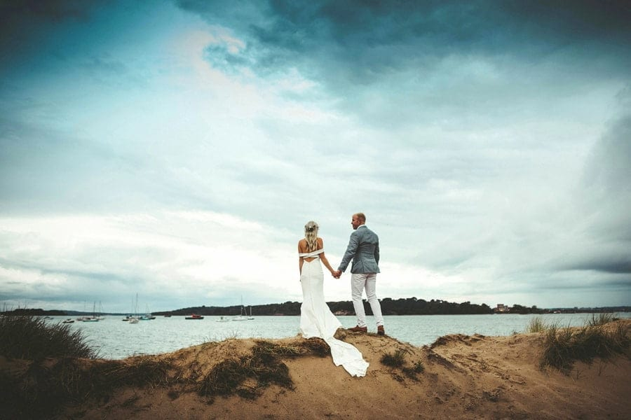 Bride and groom hold hands together on sand dunes