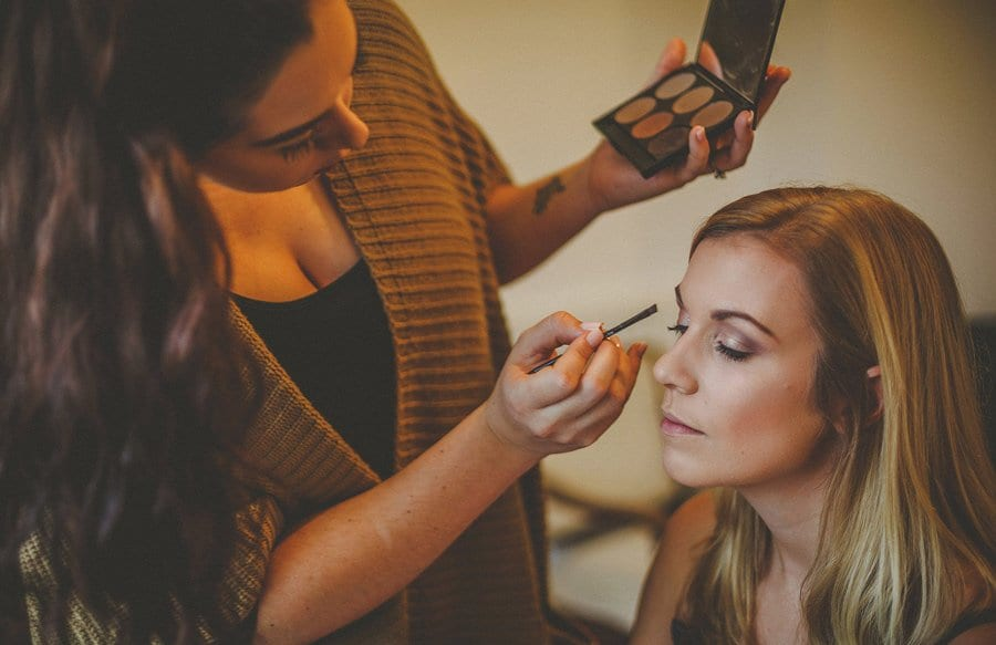 The make up artist applies makeup to a bridesmaids face