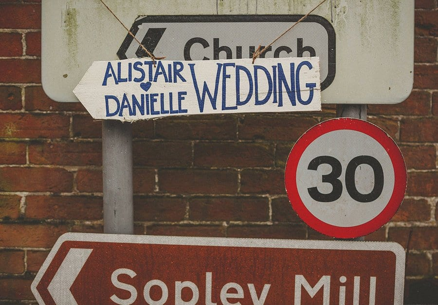 A sign hanging from a road sign showing the wedding of Danielle and Alistair