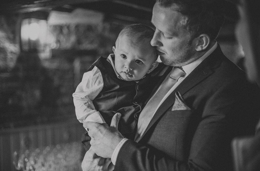 A wedding guest holds his son in his arms