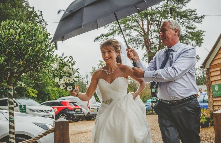 The bride arrives at Sopley Mill and a man holds an umbrella above her head