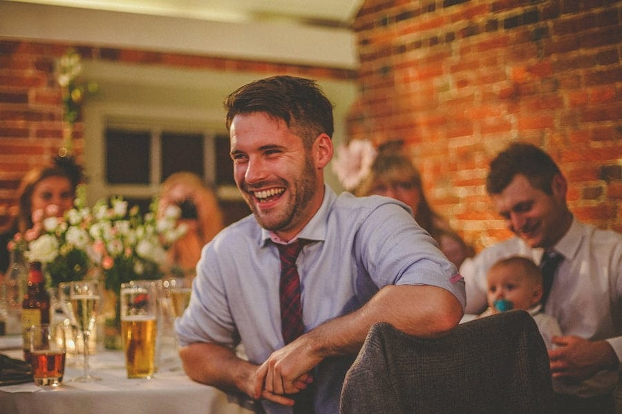 A wedding guest laughs during the best man's wedding speech