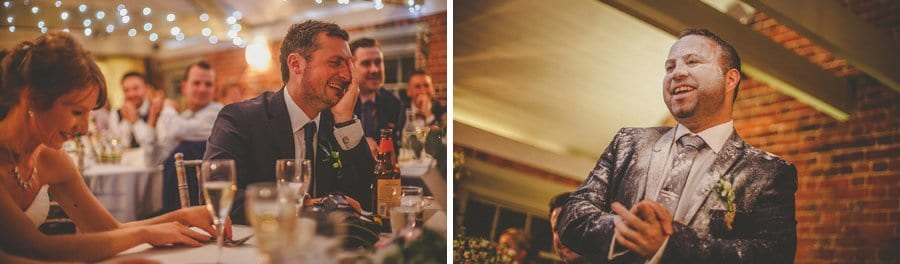 The bride and groom laugh during the best man's wedding speech