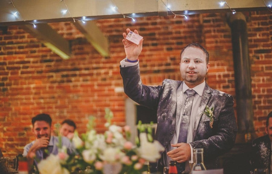 The best man holds up a driving licence during his wedding speech