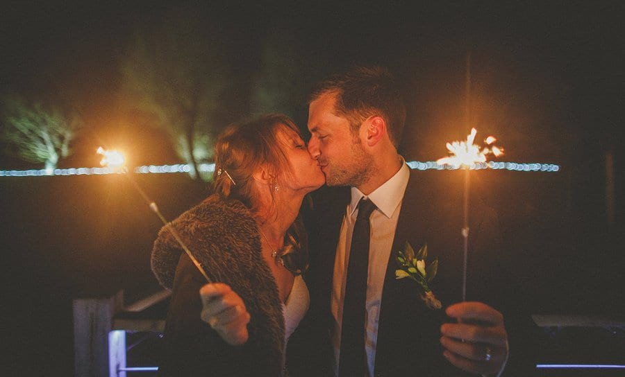 The bride and groom kiss each other and hold sparklers outside Sopley Mill