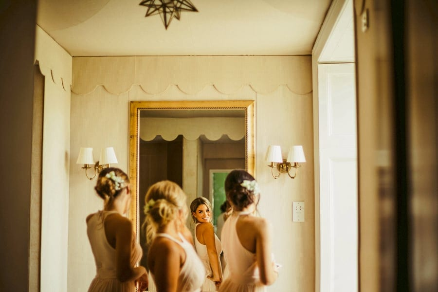 Bridesmaids looking into a large mirror hanging on a wall in the bathroom