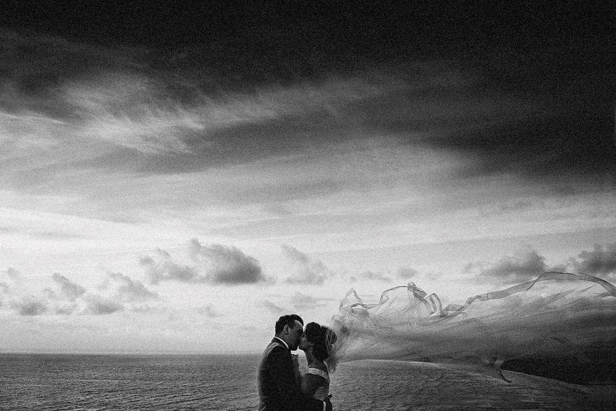 The bride and groom kiss each other in front of the sea as her veil moves in the wind