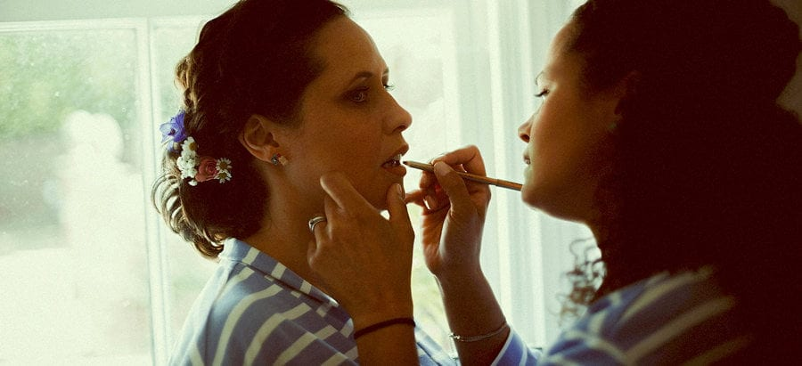 A bridesmaid applies lipstick to the brides lips next to a large window