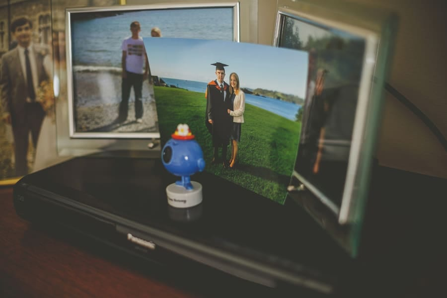 A photograph of the brides brother rests on a DVD player and other photographs