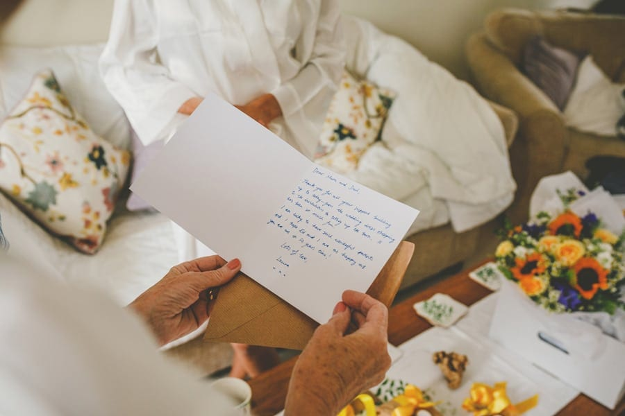 The bride's mother reads a card that was given to her by her daughter in the front room of their house