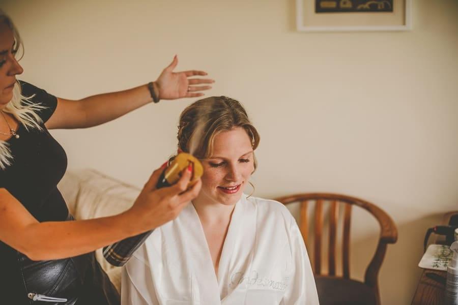 The hair stylist sprays hair spray onto the hair of a bridegroom