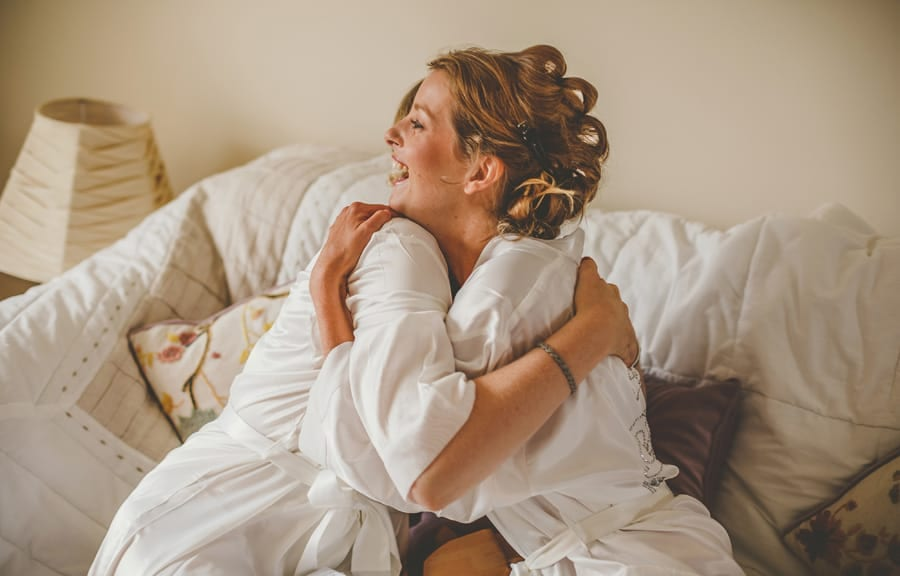 The bride and her bridesmaid embrace each other as they sit on a sofa