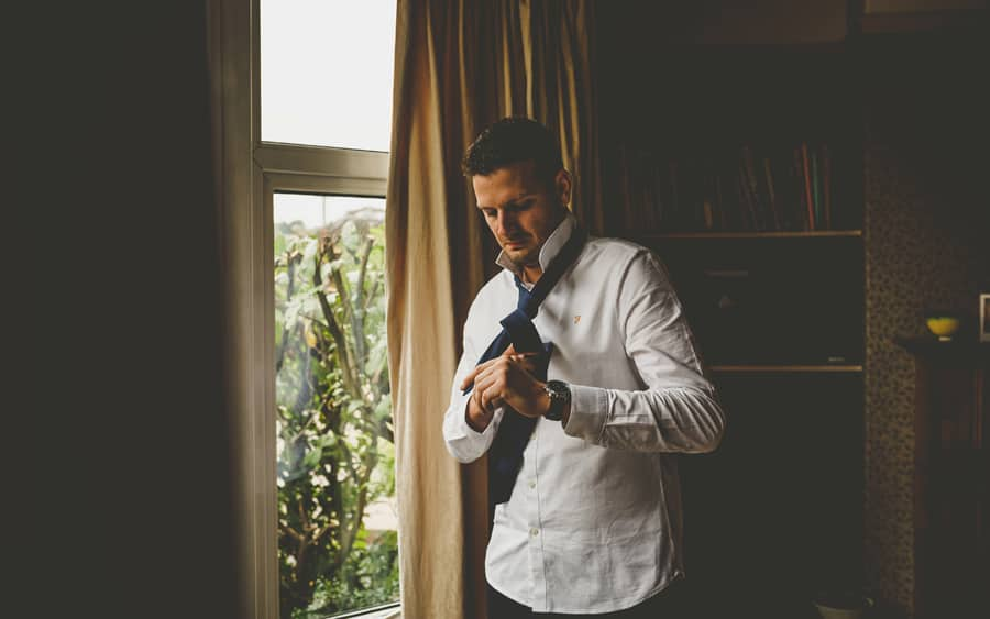 The groom stands next to a large window, looks down and puts his tie on