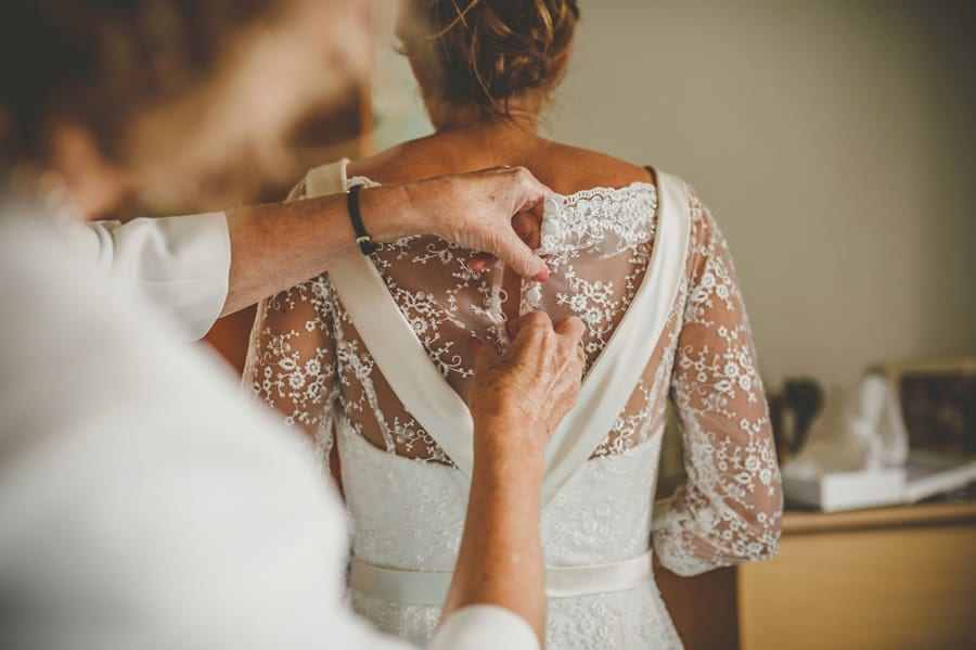 The brides mother fastens the buttons on the back of the brides dress