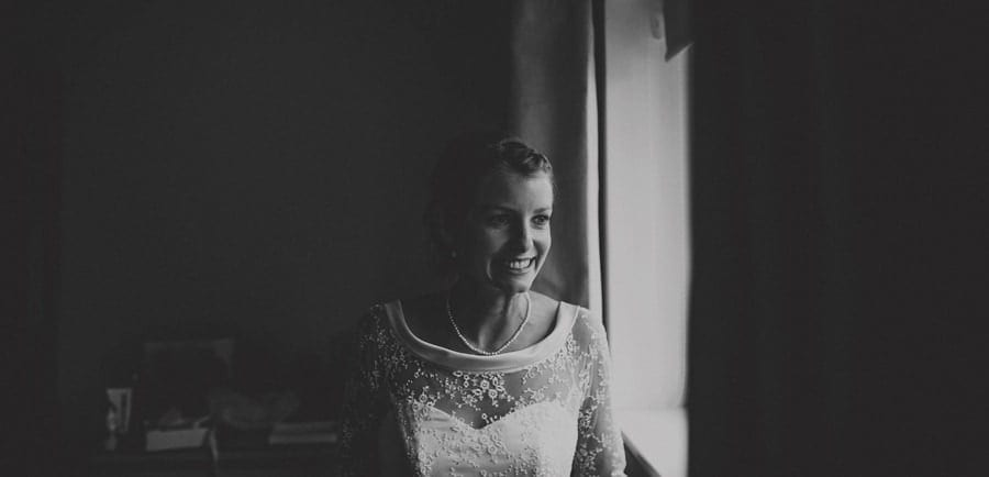 The bride smiles as she stands next to a window