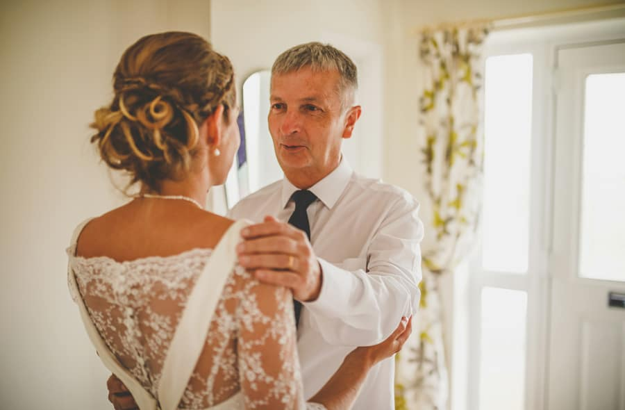 The bride's father and his daughter embrace each other at the bottom of the staircase