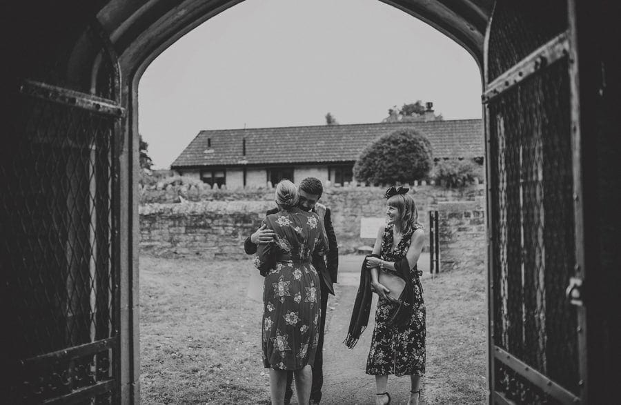 A wedding guest greets the groom's mother outside the church