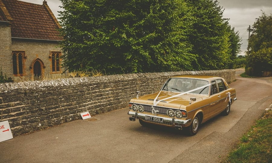 The bride and her father arrive at the church in an old car made by Ford from the 1970s