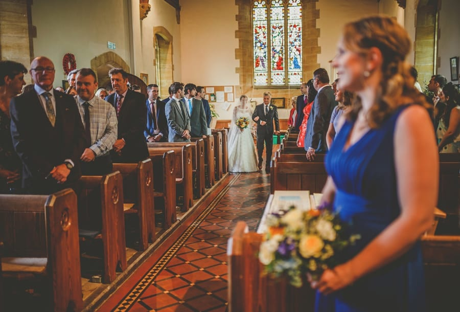 The bride and her father start to walk down the aisle of the church while the wedding guests stand and watch