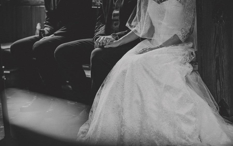 The groom holds the hand of the bride as they sit in church and listen to the wedding ceremony