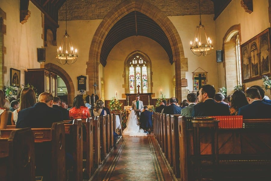 The bride and groom kneel at the alter and pray in front of the vicar during the wedding ceremony