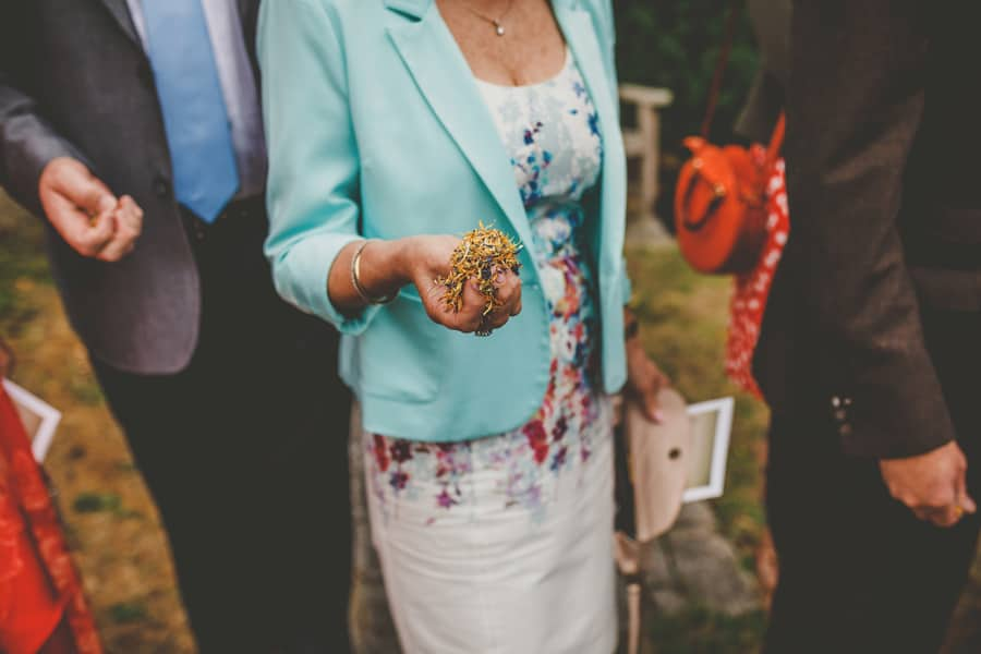 A wedding guest holds confetti in her hand