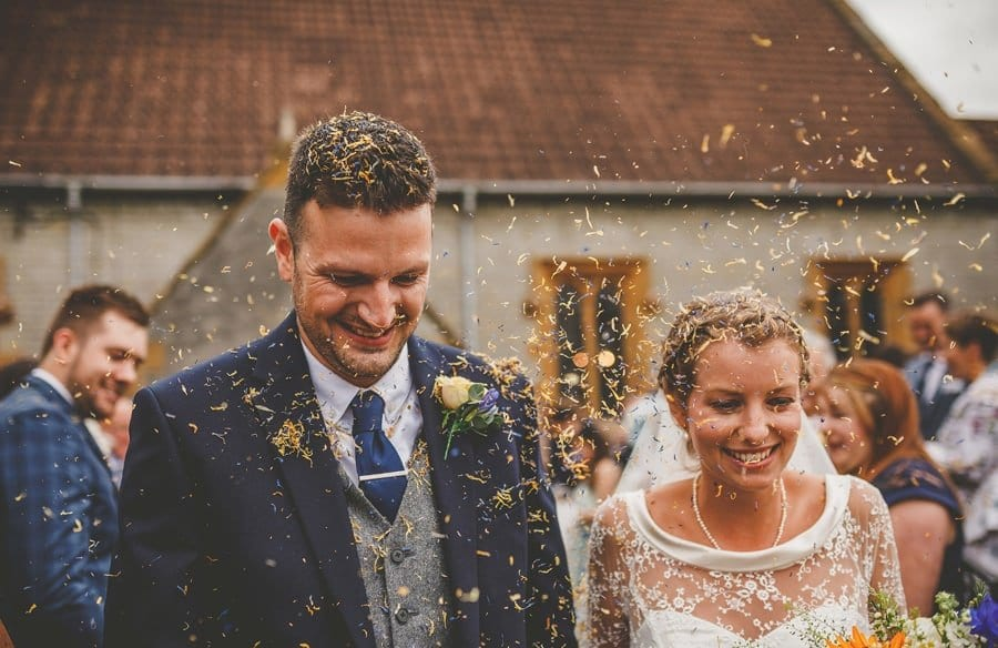 Confetti falls onto the bride and groom as they walk down the path of the church