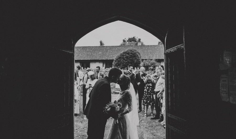 The bride and groom kiss each other at the entrance to the church as the wedding guests stand outside