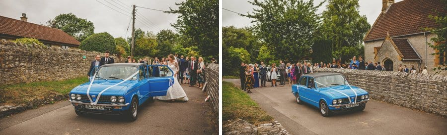 The bride and groom enter a car and drive away from the church as wedding guests stand and watch