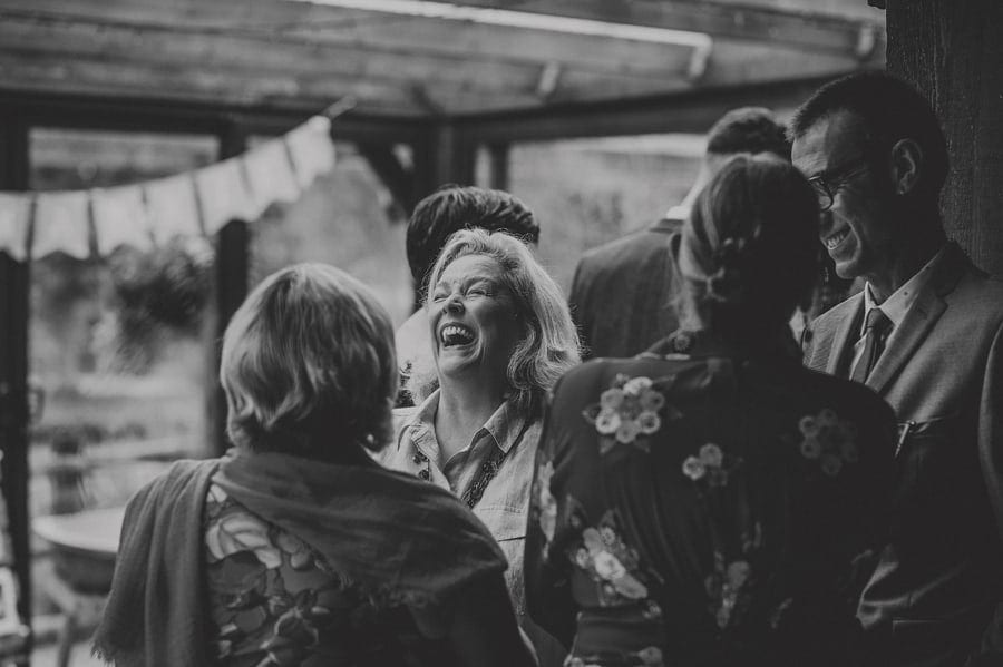 A wedding guest closes her eyes and laughs as she talks to friends at Yarlington barn in Somerset