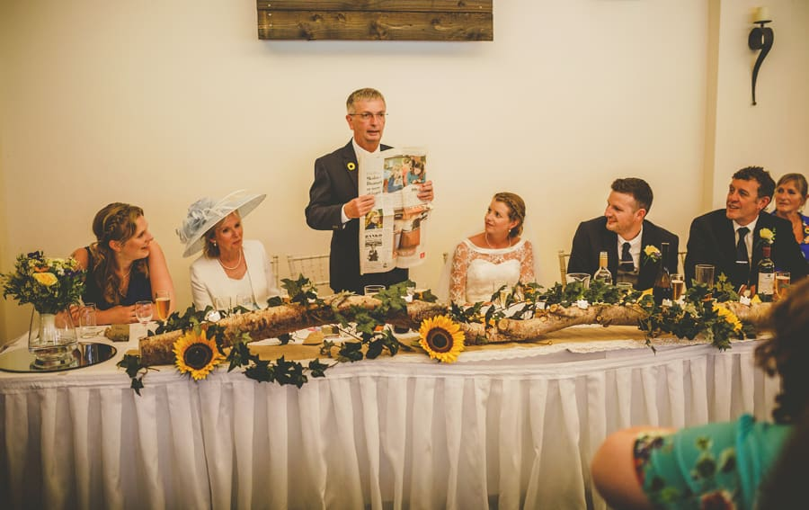 The bride's father holds a newspaper up and delivers his speech to the wedding party at Yarlington barn in Somerset