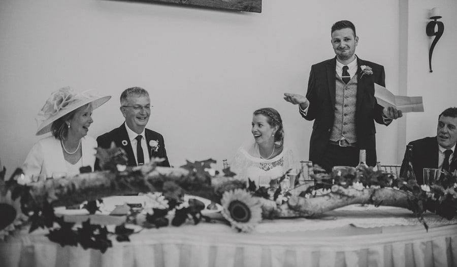 The groom delivers his speech to the wedding guests as the family are sat at the wedding table